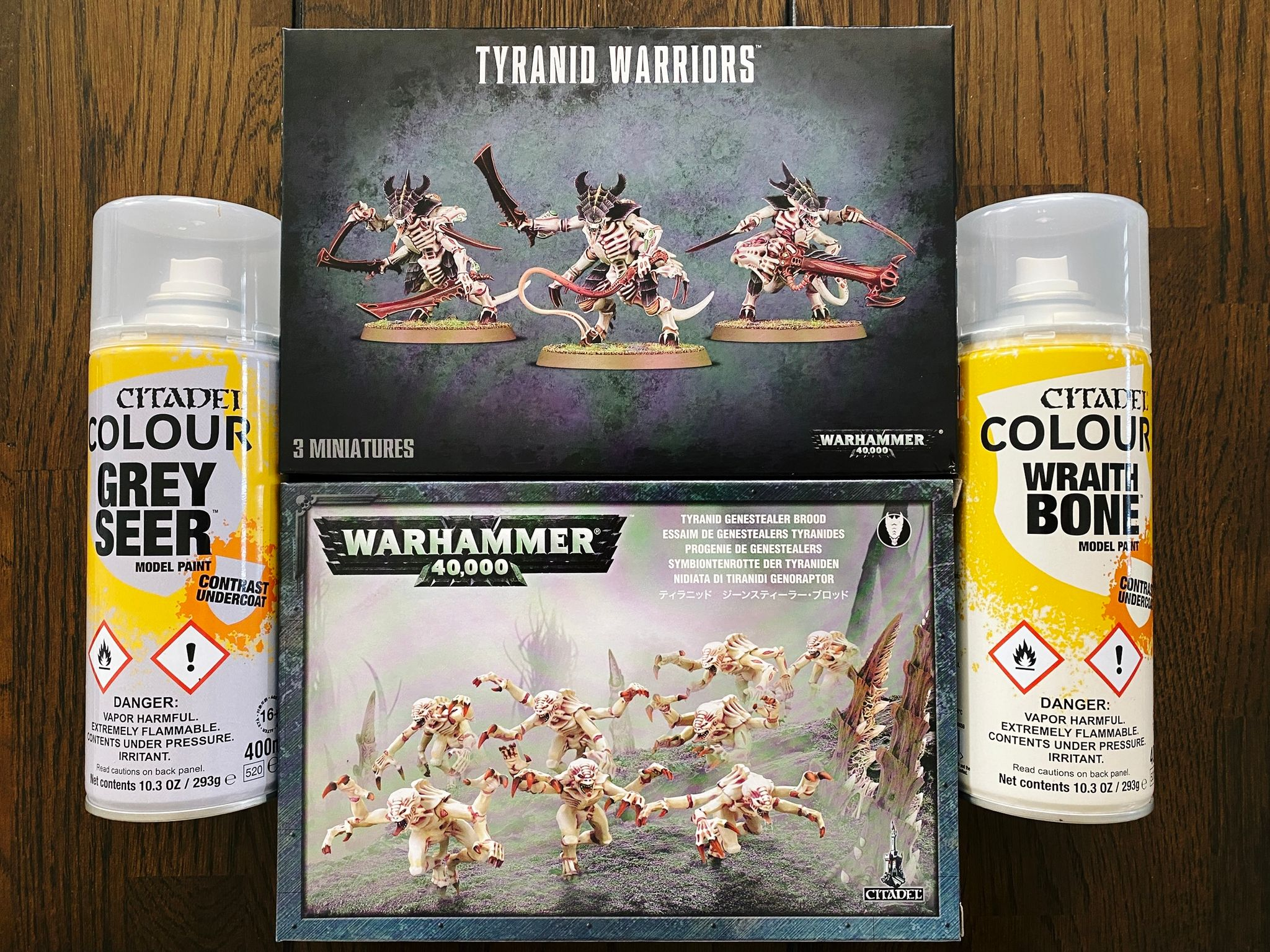 A photo of two cans of Games Workshop undercoat spray paints, a box of Tyranid Warriors (four-armed Aliens-esque towering freaky alien things) and a box of Genestealers (also four-armed freaky alien things, but smaller and more hunched over).