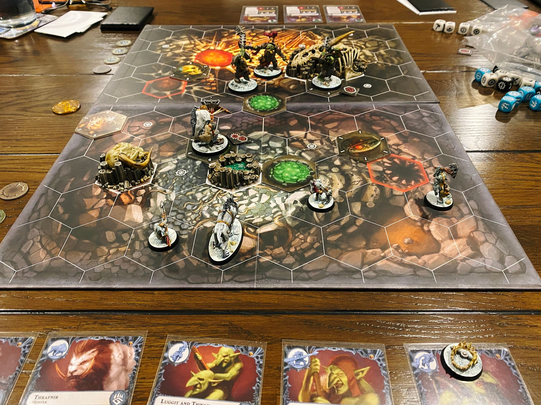A photo of a Warhammer Underworlds game board, it has tiled hexes on it and the art on the board looks like a cave. The miniatures are 3 heavily-armoured orruks (orks) on Kristina's side, and on mine are 3 gnoblars (goblins), a sabretooth tiger, and Hrothgorn who is a huge ogre with a massive crossbow.