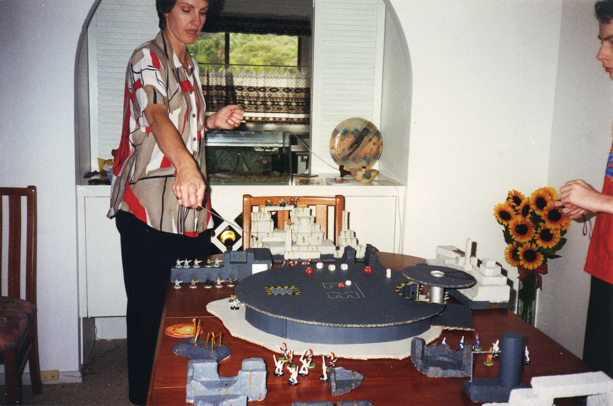 A photo of our dining room table with a bunch of crummy polystyrene terrain on it but also an enormous landing pad made out of cardboard, and lots of miniatures. My mum, a tall white woman with a very mid-90s short but poofy hairdo, is standing gesticulating at the table with a tape measure.