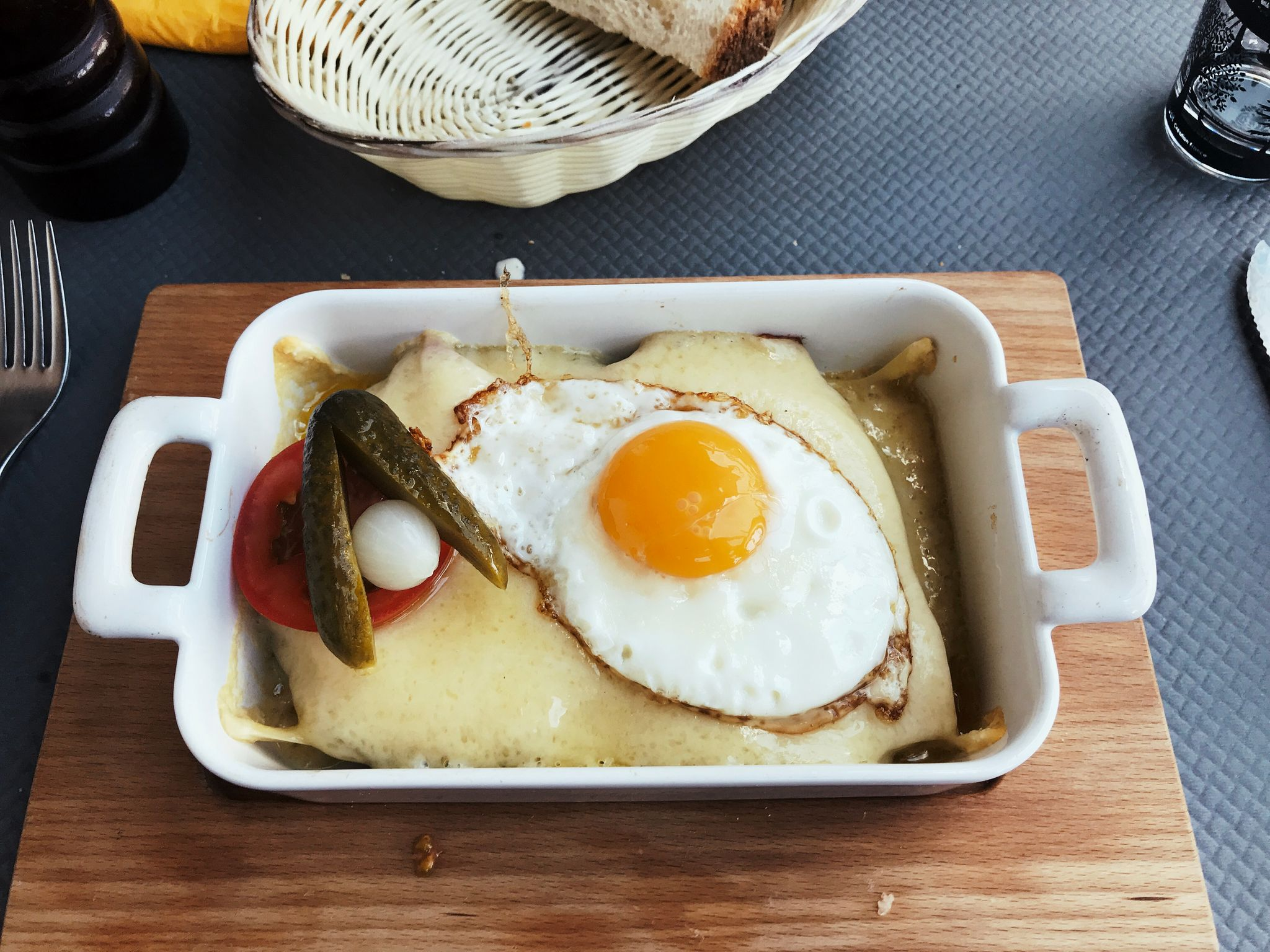 A photo of a rectangular white ceramic dish that appears to contain almost nothing but melted cheese. On top is a pickle, a slice of tomato, and a fried egg.