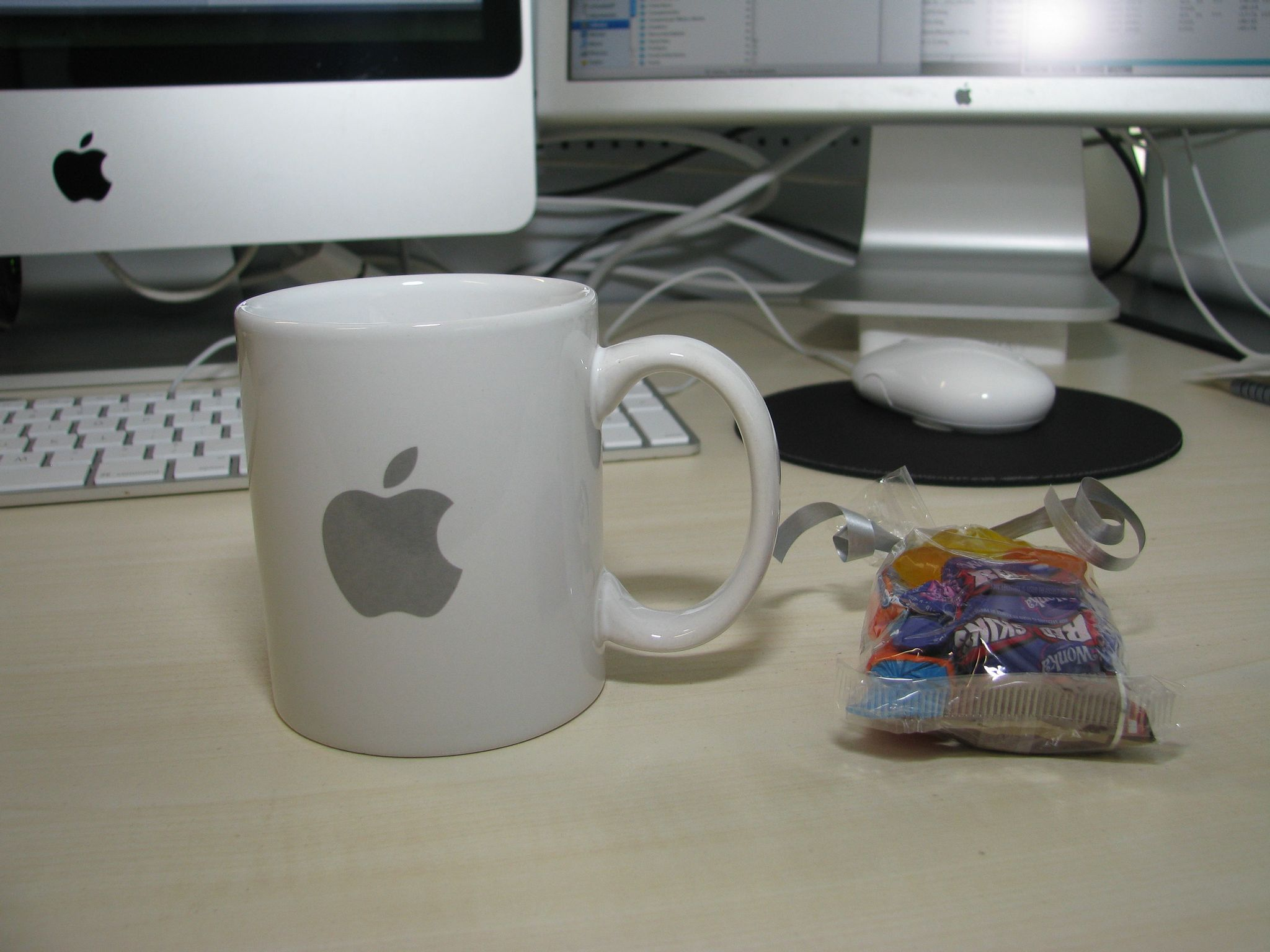 A photo of a white coffee mug with a grey Apple logo on it sitting next to a small bag of lollies.