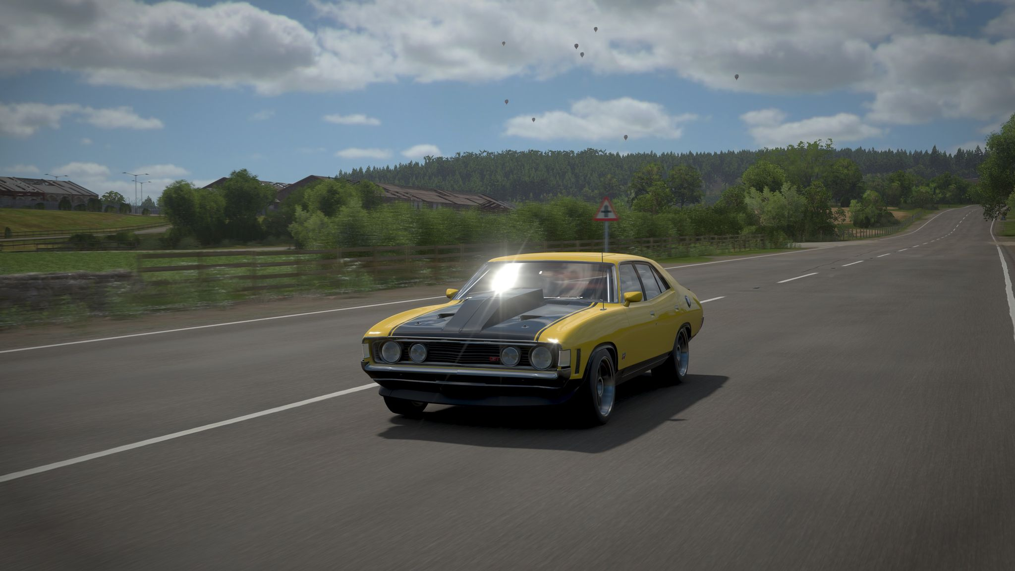 A screenshot from Forza Horizon 4 showing a GT-HO Falcon driving down a long empty road with trees and fields on either side.
