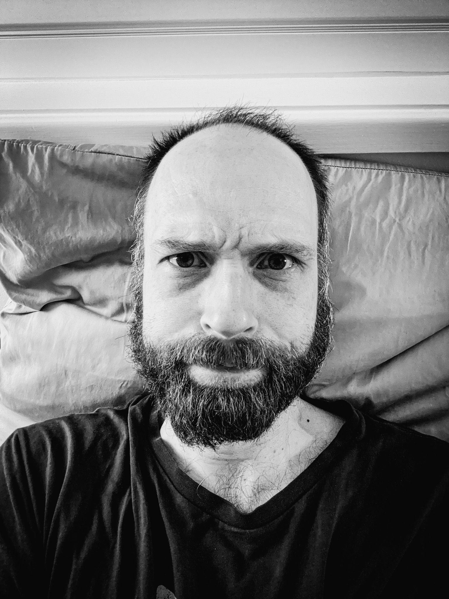 """A black and white selfie of me, a white man with a scruffy beard and, uh, let's say """"large forehead"""" rather than """"receding hairline"""", with my eyebrows furrowed looking intently at the camera."""