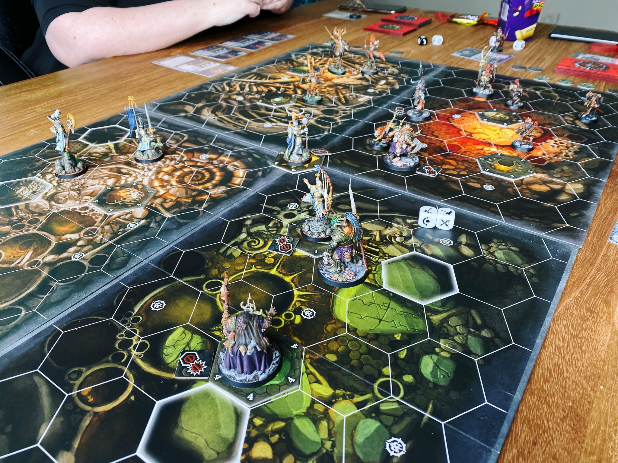 A photo of a four-player game of Warhammer Underworlds. There's four boards with hexagonal tiles marked on them connected together with plenty of miniatures in the middle of combat.
