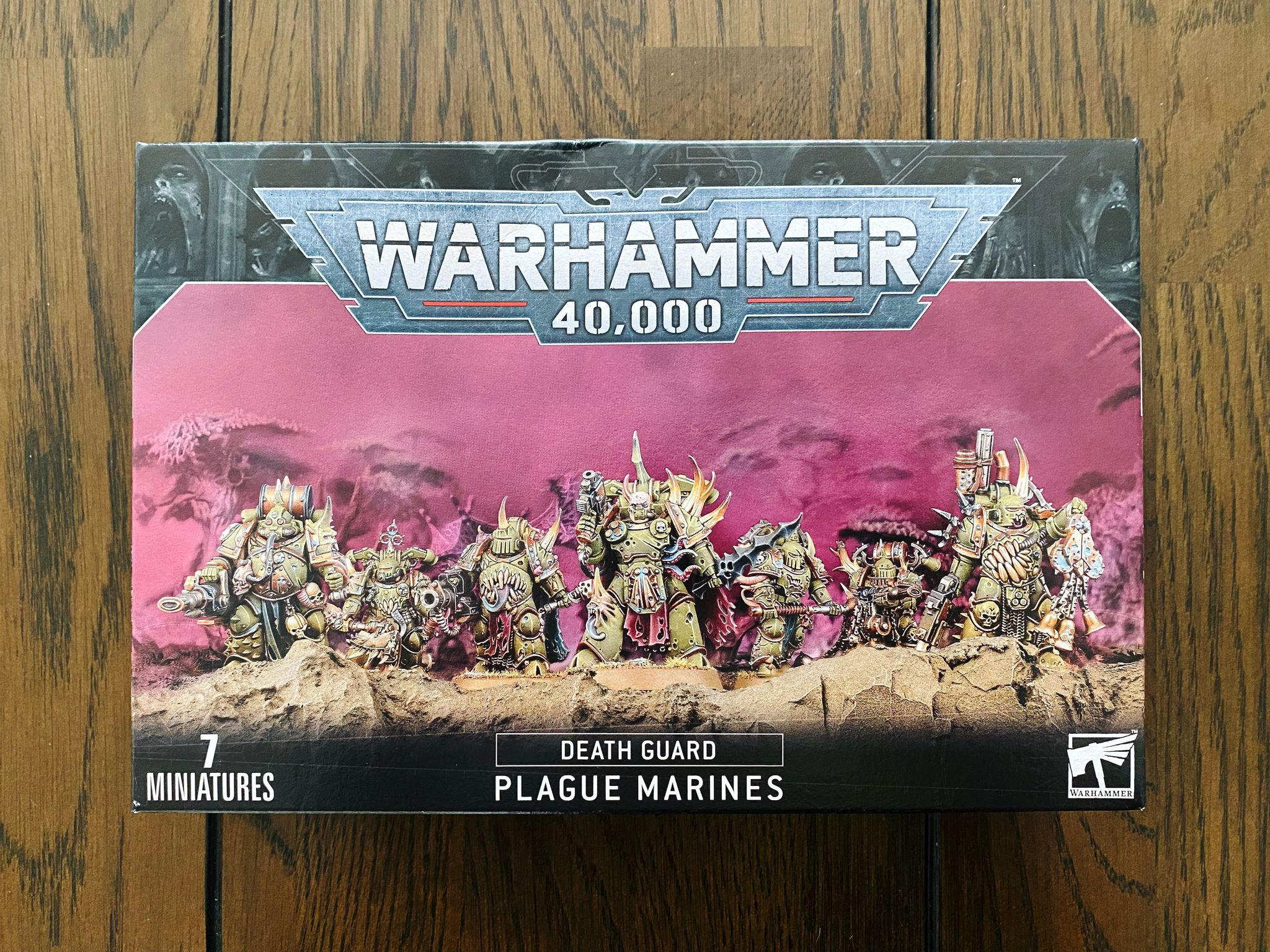 A photo of the box set of seven Plague Marines from Warhammer 40,000. They're all big and heavily armoured with all sorts of tentacles and gross fleshy bits coming out of them.