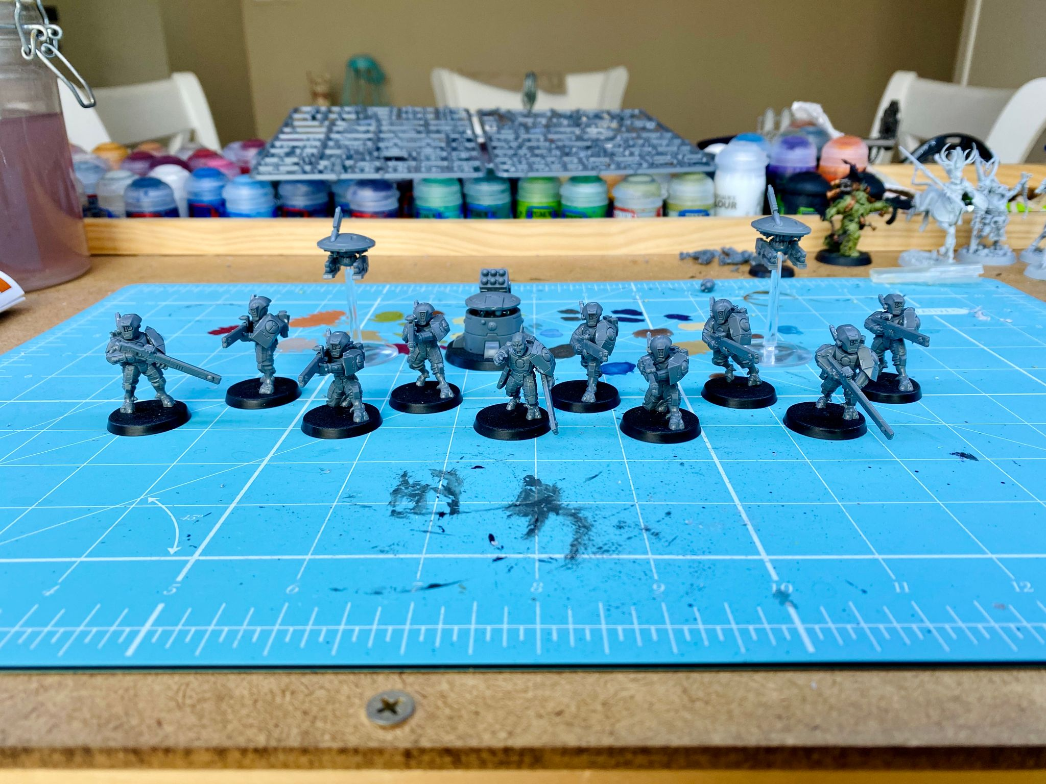 A photo of a squad of Tau from Warhammer 40,000 Kill Team. Nine Fire Warriors, one Fire Warrior sergeant, two drones, and a tactical support turret. They're all unpainted, just grey plastic.