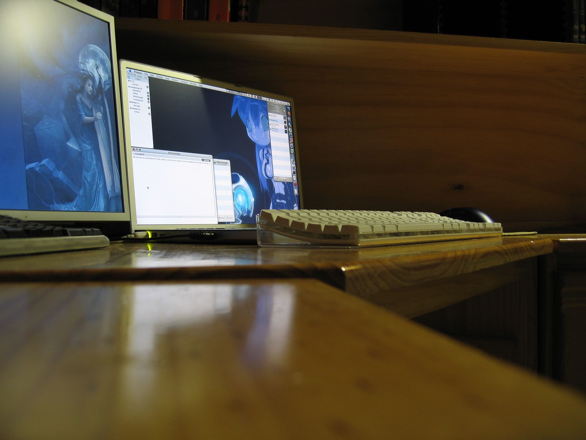 "A photo taken with the camera sitting on a desk looking towards a 17"" PowerBook G4 flat on said desk, with a white Apple keyboard in front of it and a 17"" 4:3 display to the left of it, hard against the PowerBook's side."
