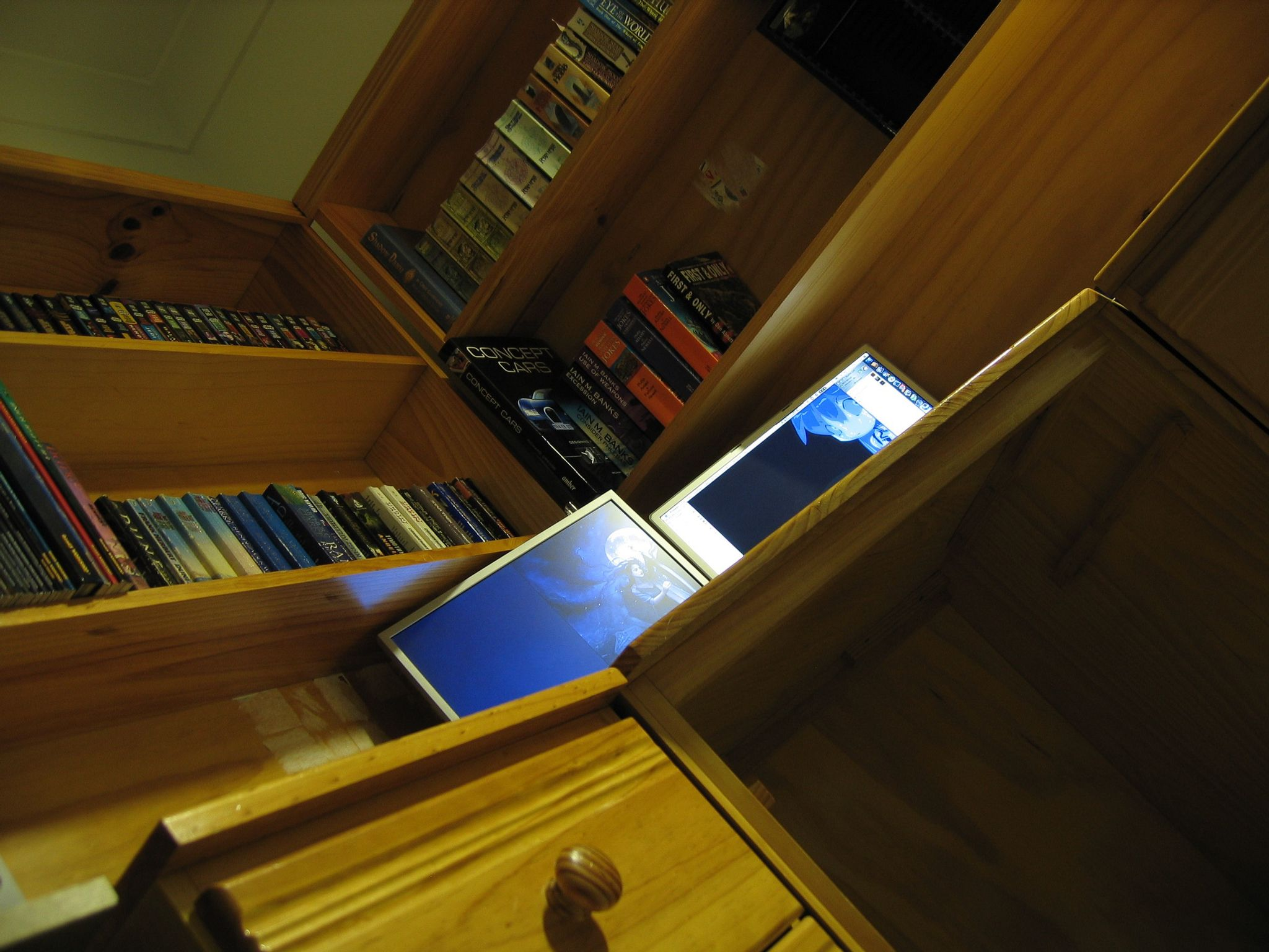"A photo taken from nearly floor level and at an angle looking up at a corner desk. On the desk are bookshelves filled with books, and just visible on the desk itself is the top of a 17"" PowerBook G4 and a 17"" 4:3 display to the left of it."