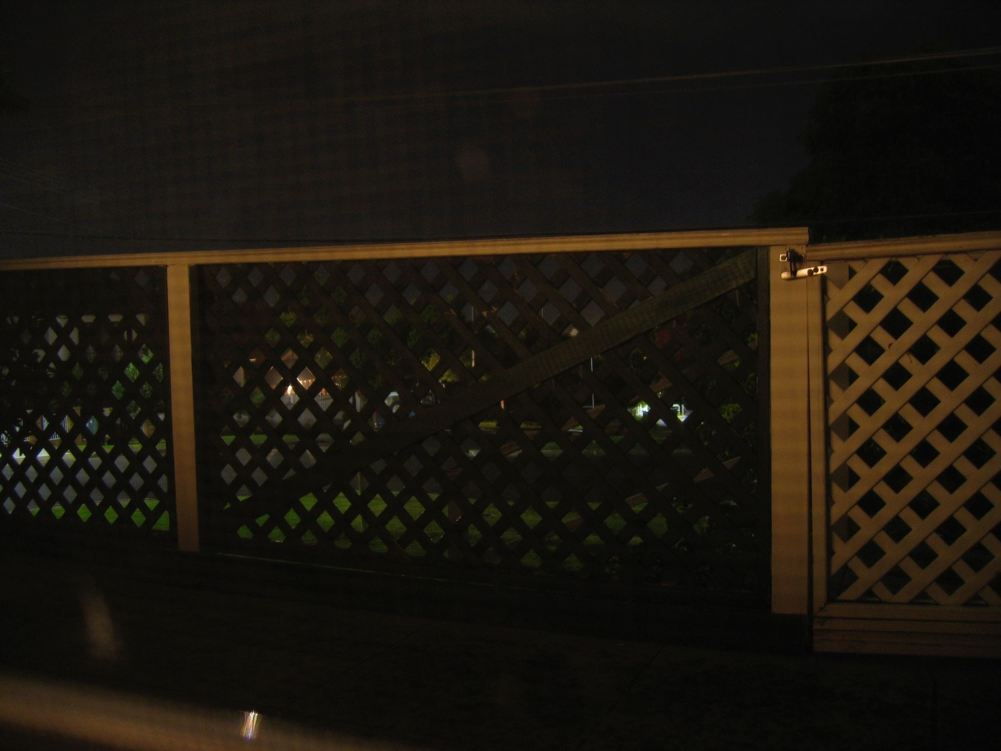 A very under-exposed nighttime photo of the lattice on the front of a balcony, looking out at the night.