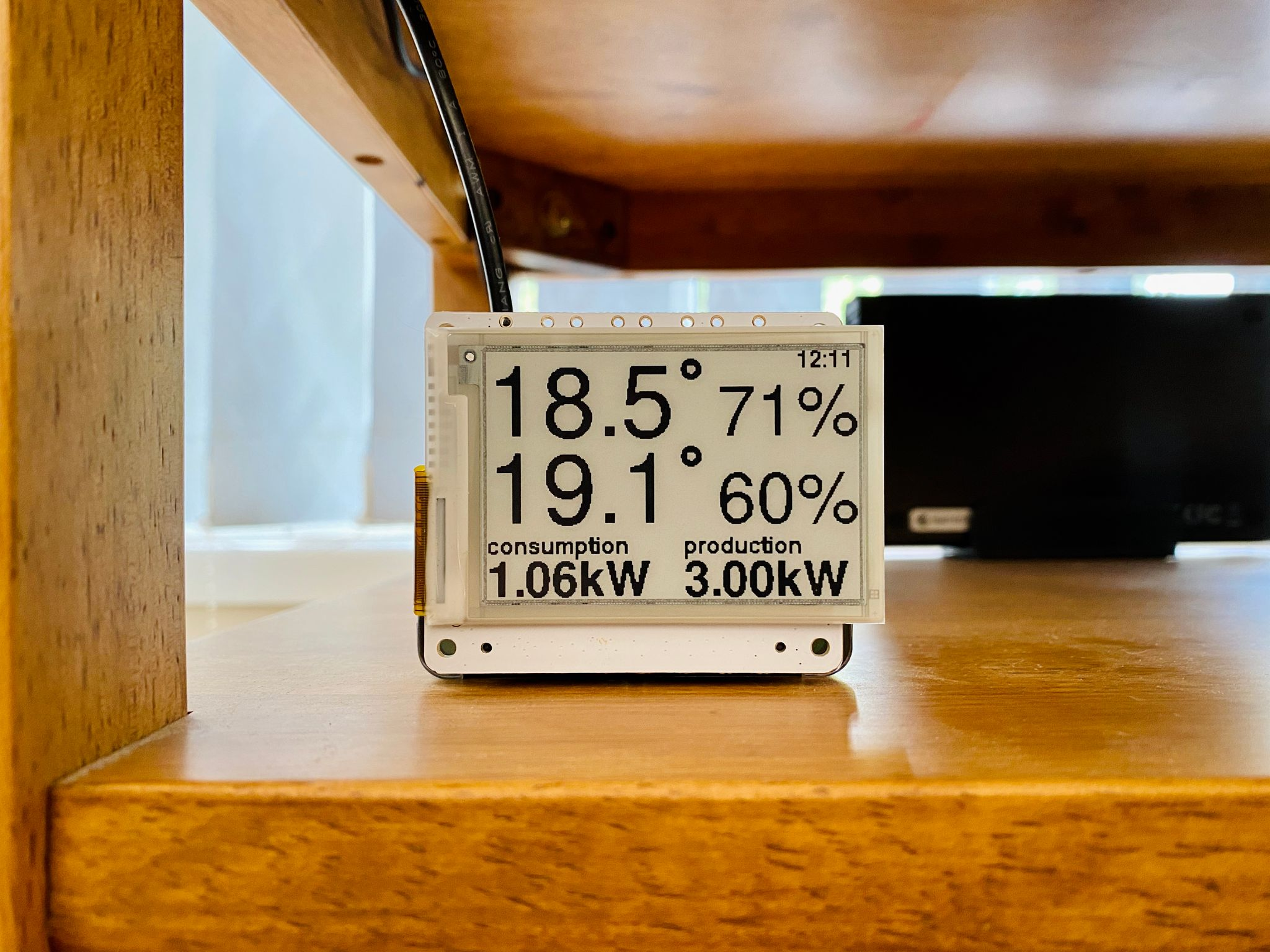 A photo of a small e-ink display on a shelf showing the current outdoor and indoor temperatures, plus current power consumption and production in kilowatts.