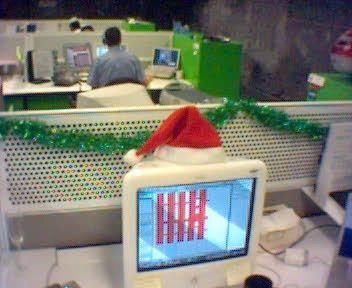 A photo of an Apple eMac computer with a santa hat on it, and green tinsel strung along the desk divider behind it.