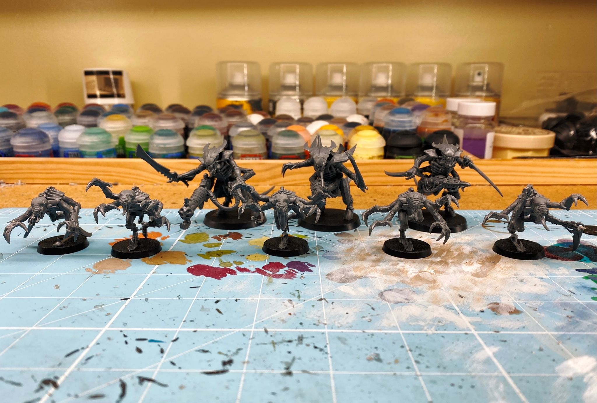 A photo of three Tyranid Warriors (huge hulking Aliens-eque miniatures that have four arms and are all covered in chitin, all their weapons are biological as well) and five Genestealers (smaller hunched-over Aliens-esque miniatures who also have four arms, which end in either giant talons or sword-looking things that are also actually part of their arms).