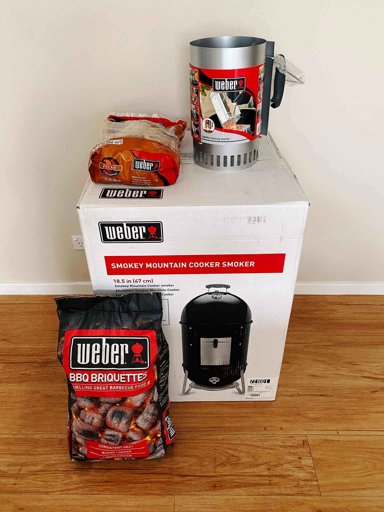 "A photo of a Weber ""Smokey Mountain"" smoker in its box, along with a bag of barbecue briquettes, pecan wood chunks, and a charcoal chimney."