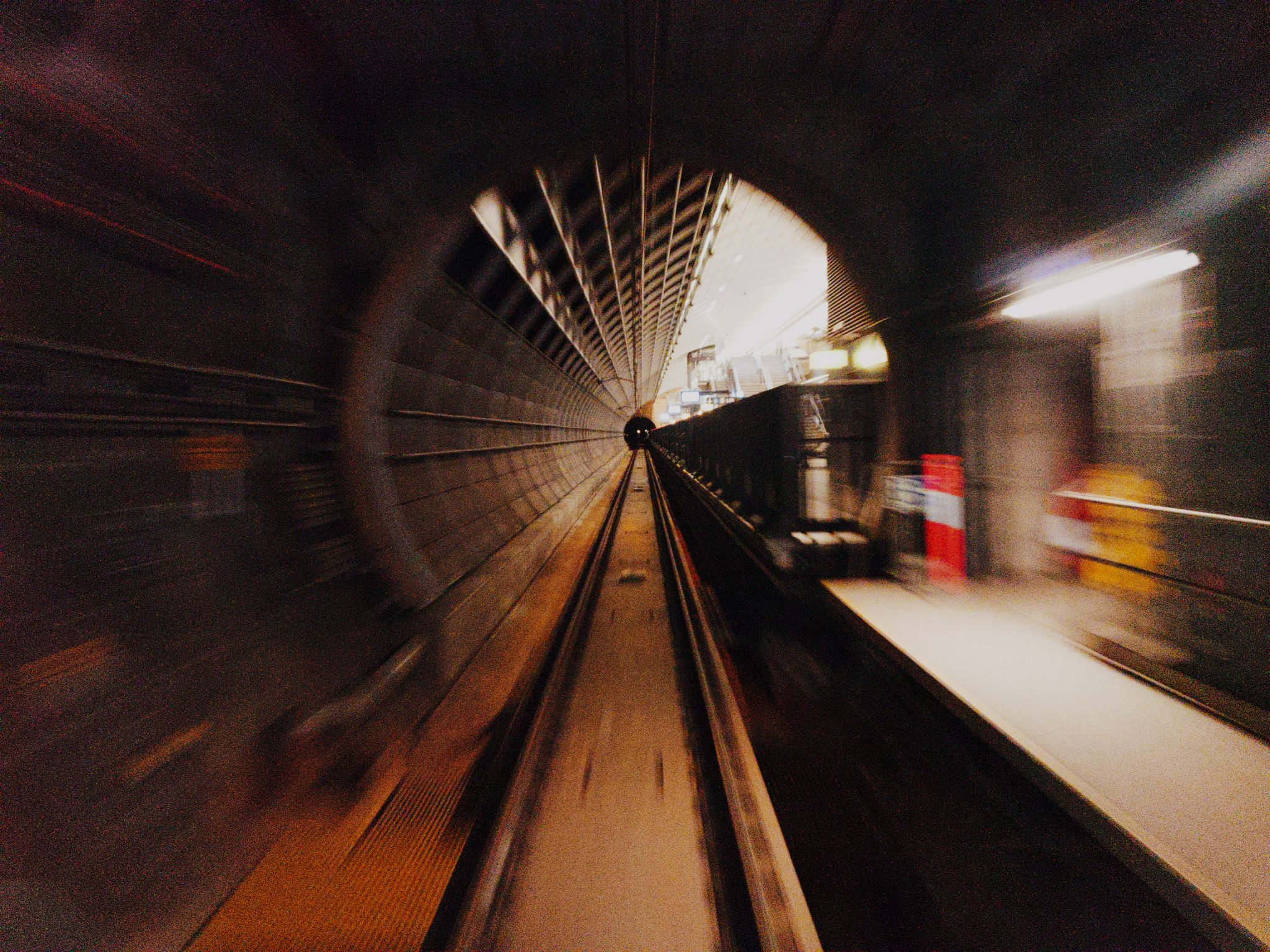 A motion-blurred view from the front of a train as it shoots through a round-profile tunnel. It's just about to emerge into a train station.