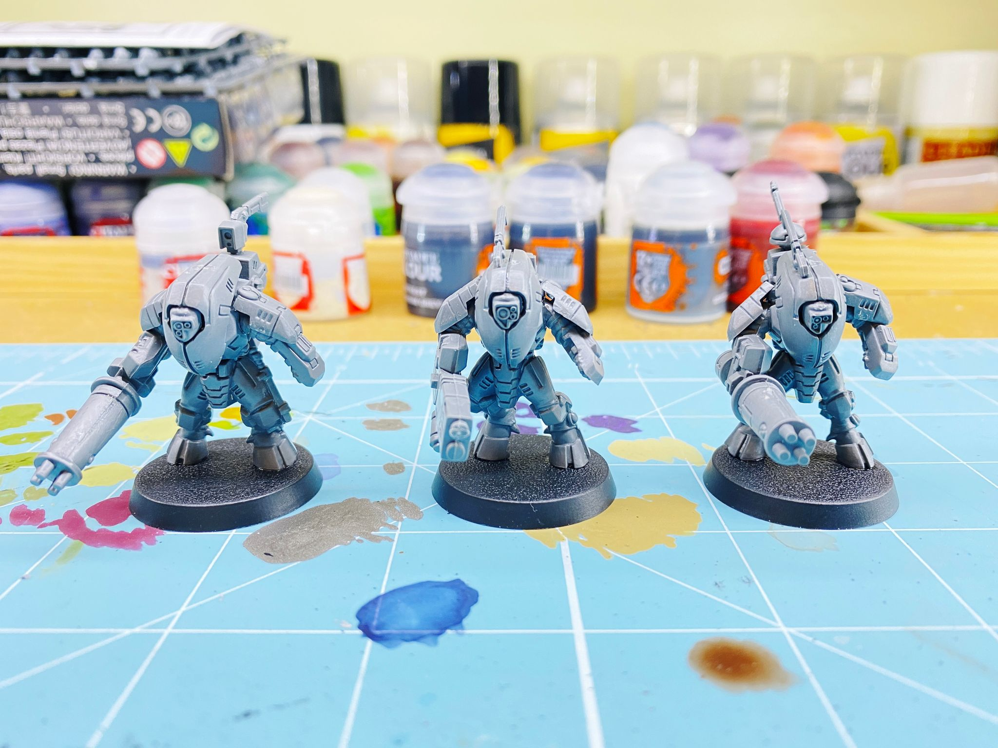 A photo of three assembled but unpainted grey plastic miniatures. They're bulky-looking robot suits with huge guns on one arm. (Yes, they _are_ called Stealth Suits despite being the least stealthy-looking things you could think of!)