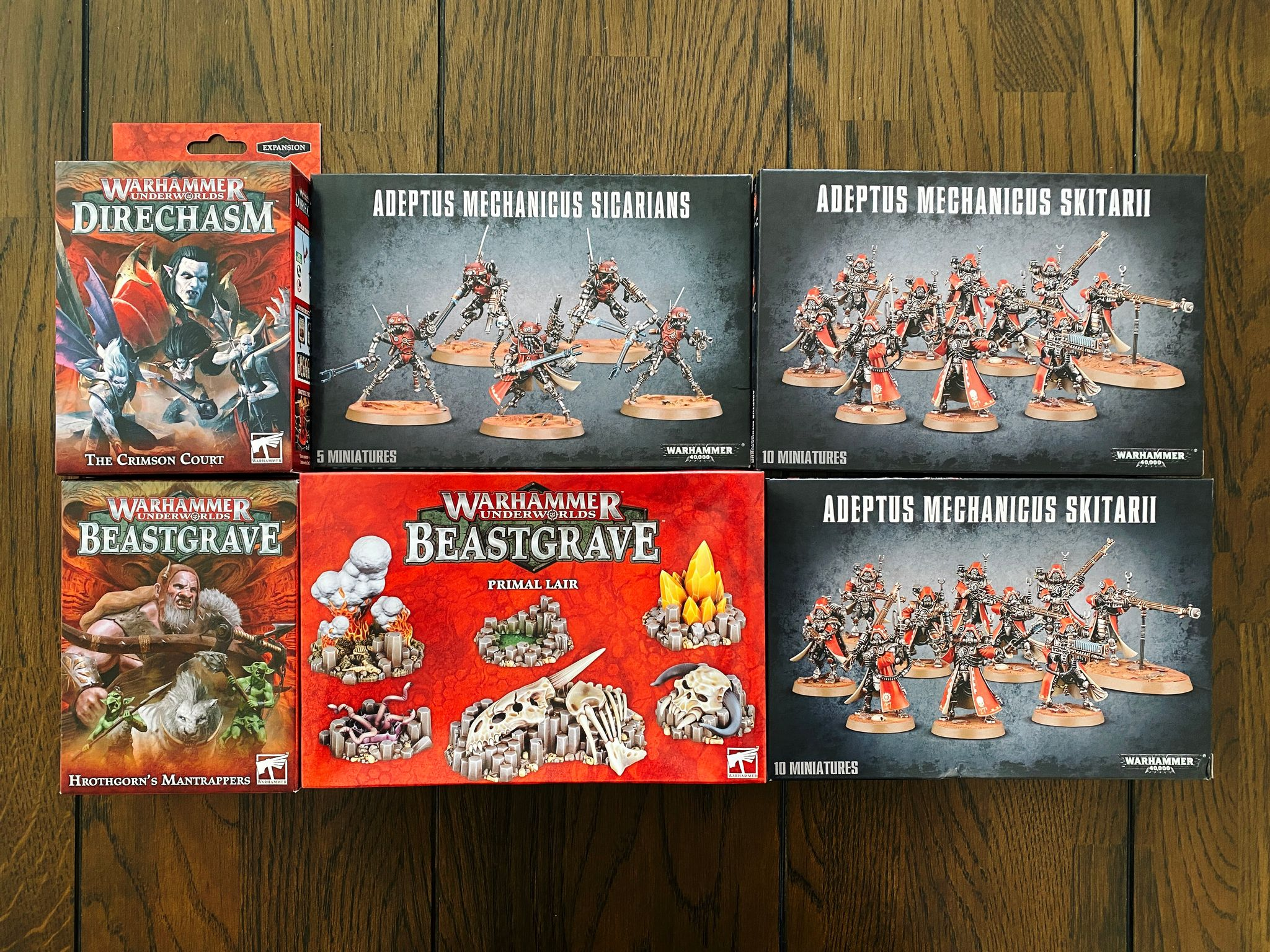 "A photo of a bunch of boxes of Games Workshop miniatures: for Warhammer Underworlds, two warbands (Hrothgorn's Mantrappers and the Crimson Court) and the ""Primal Lair"" terrain pieces from Beastgrave, and for Warhammer 40,000, Adeptus Mechanicus (two boxes of Skitarii and one box of Sicarians)."