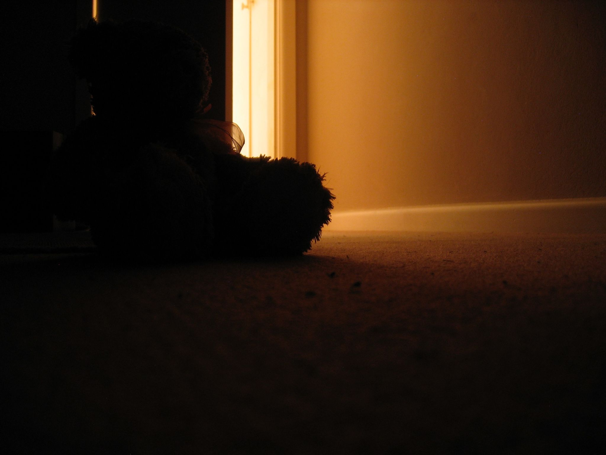 A long exposure photo looking out towards a partially-closed door, taken with the camera sitting on the floor. The room is dark and there's very warm light coming in from the doorway. A soft toy of some sort is visible against the door, only the edges of it are lit.