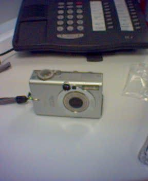 An EXTREMELY poor quality photo from a 2004-era mobile phone of a silver compact point-and-shoot camera.