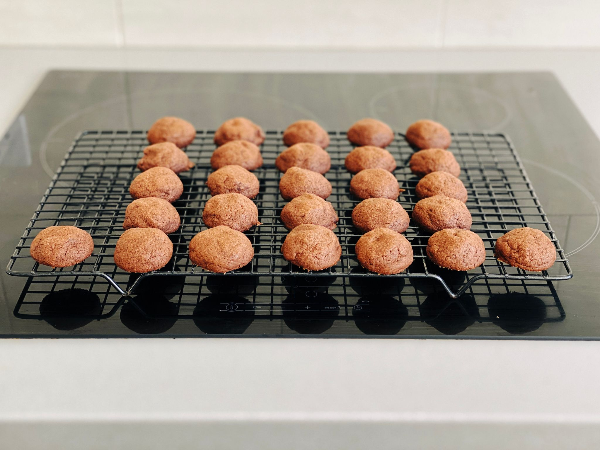 A photo of a batch of small round button-shaped chocolate cookies sitting on a cooling rack.