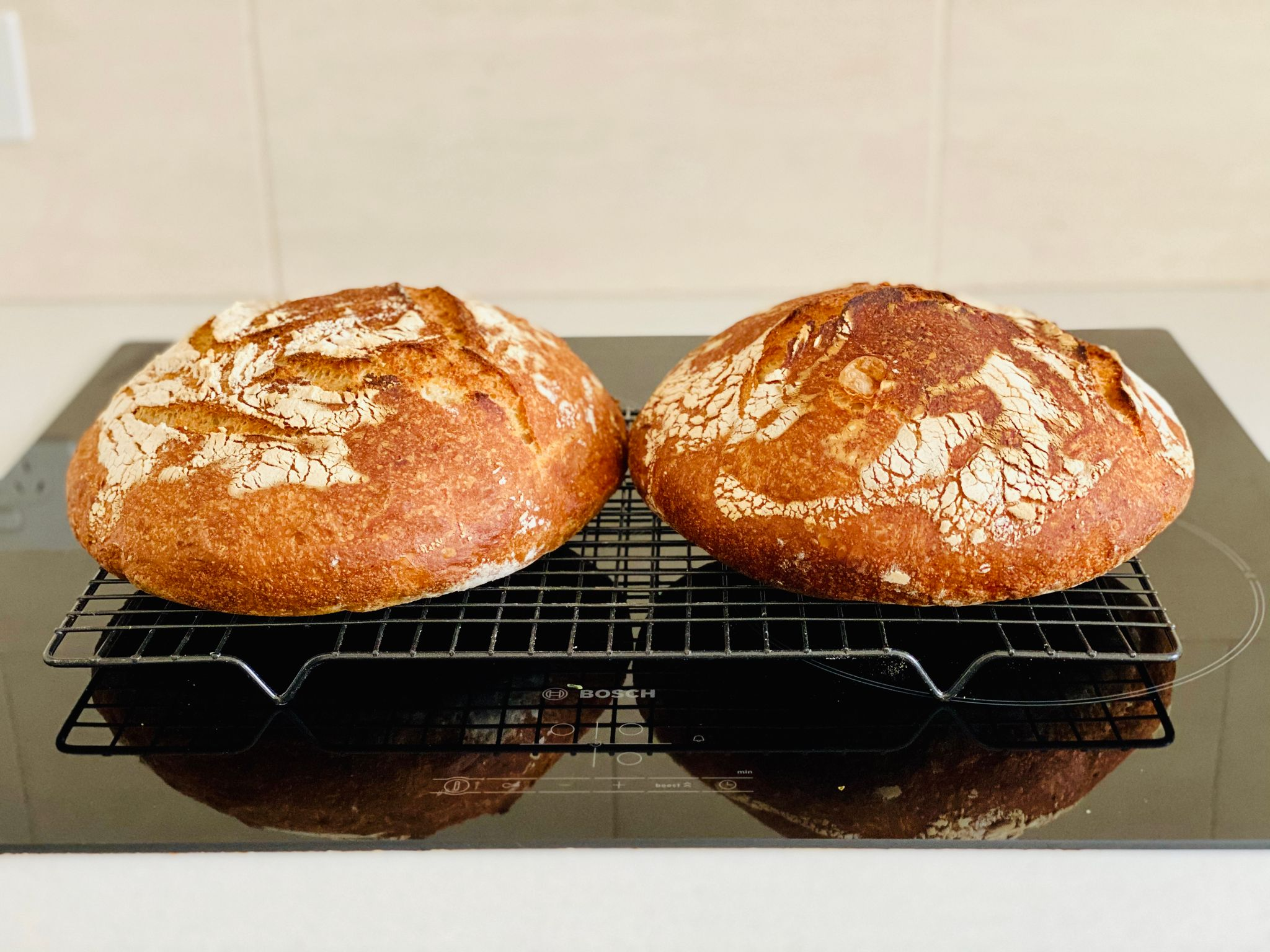 Two round brown loaves of bread sitting on a cooling rack.