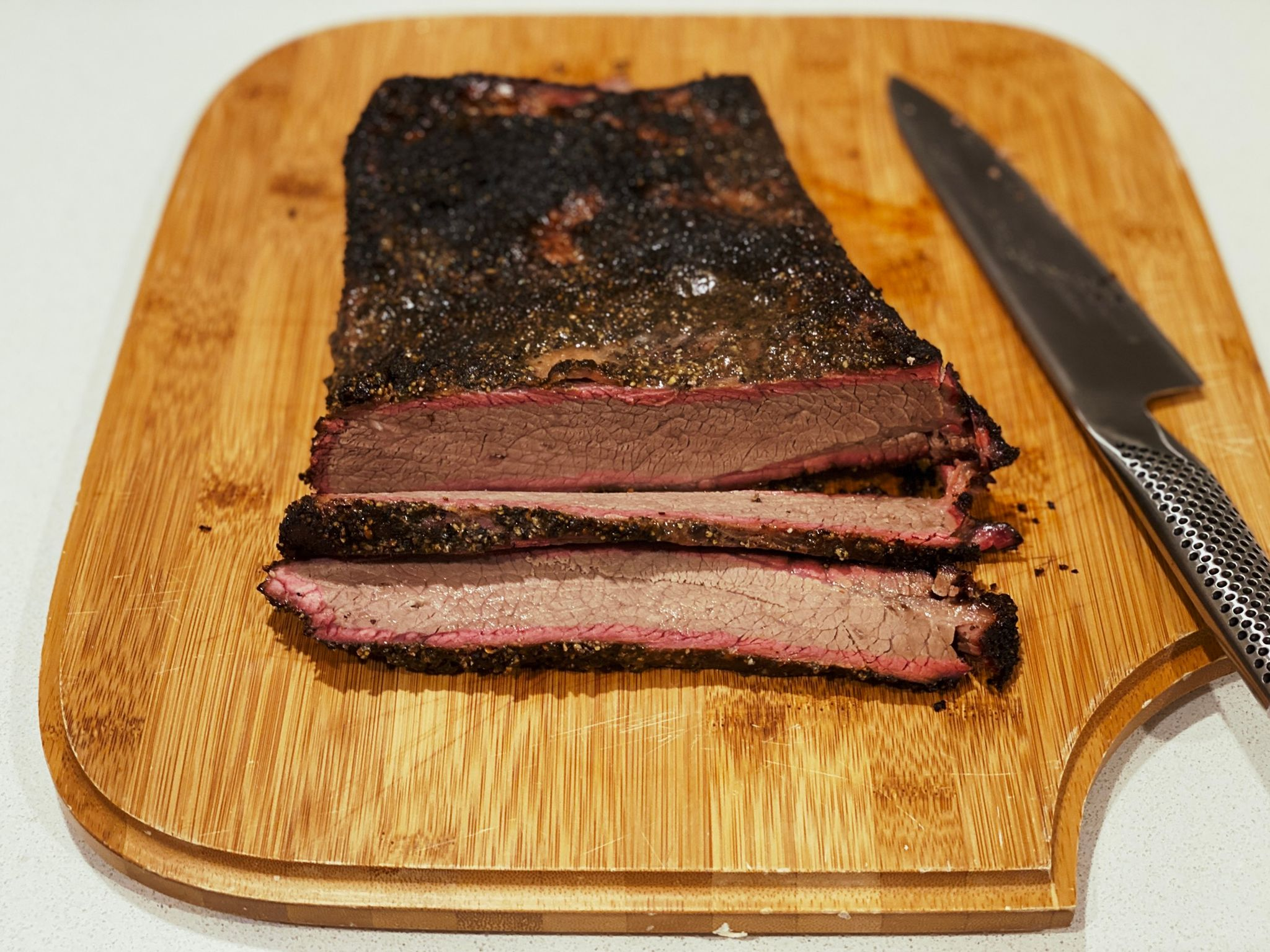A photo of a cooked beef brisket sitting on a cutting board, with two slices have been done and a fantastic smoke ring visible.