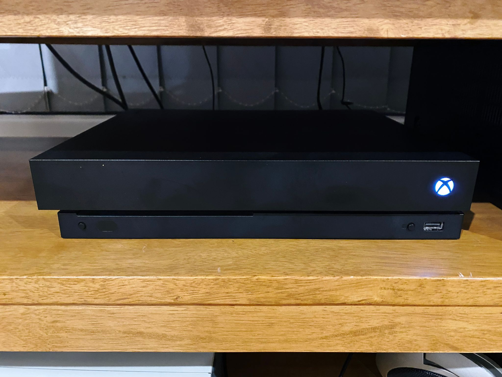 A photo of an Xbox One X sitting on a wooden shelf.