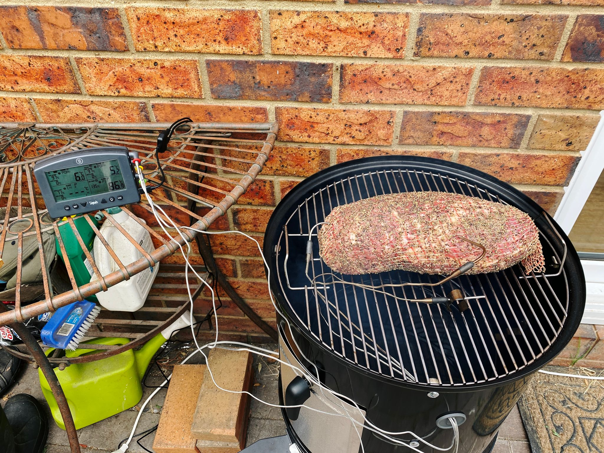 A photo of a big chunk of meat on a smoker, with temperature probes going into it.