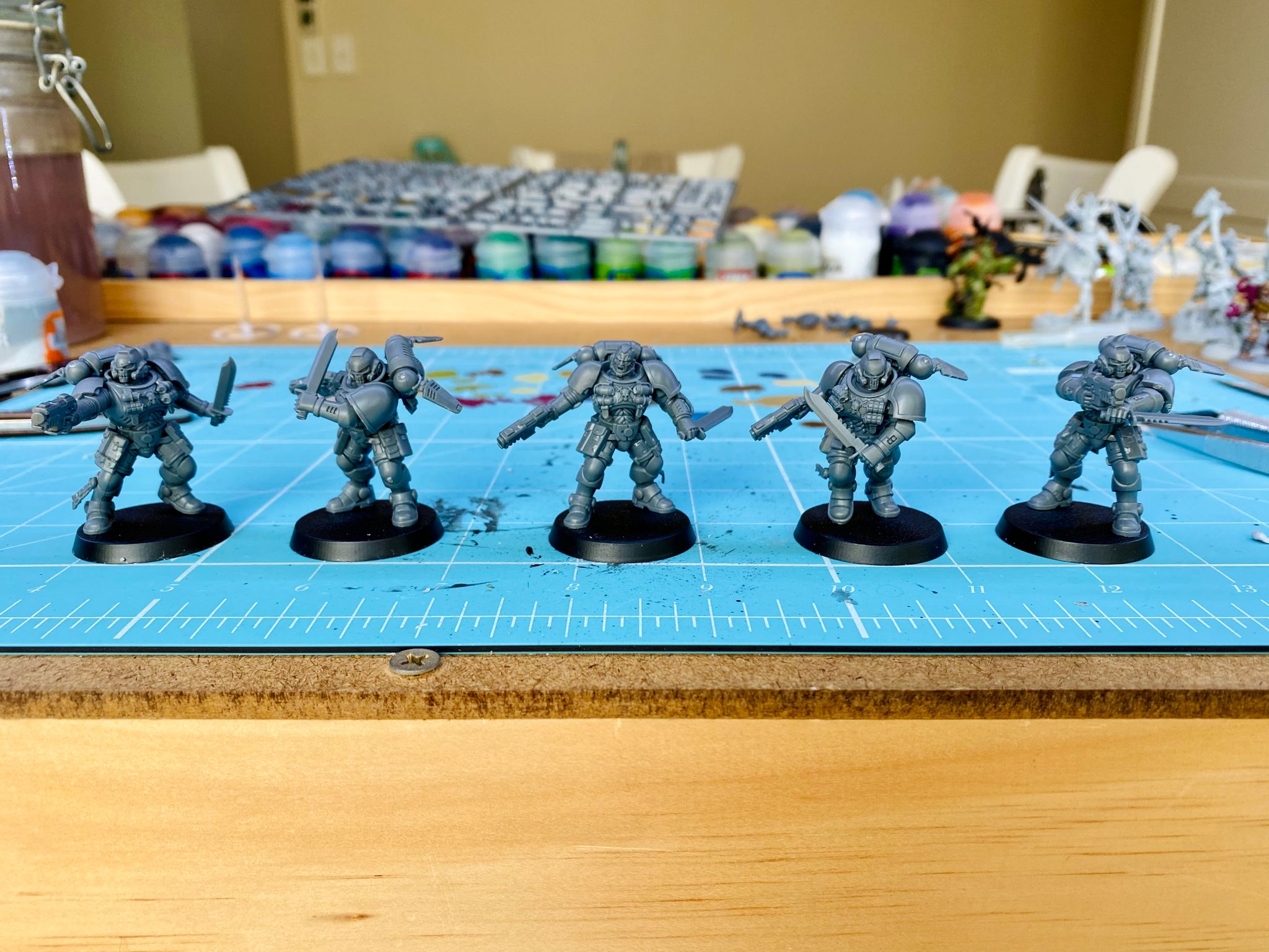A photo of five assembled but unpainted Space Marine close combat specialists from the Warhammer 40,000 Kill Team box. They're all armed with bolt pistols and combat knives and are in various dynamic poses like they're in the middle of moving or shooting during a battle.
