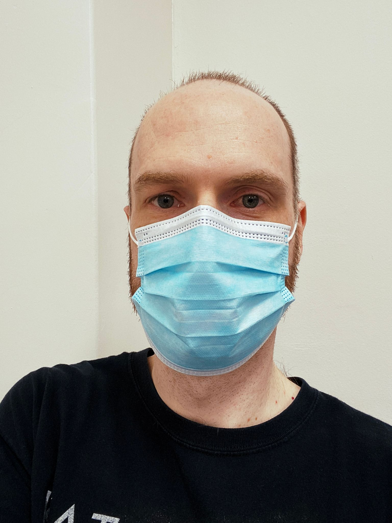 A photo of a white man with short hair wearing a blue surgical mask.