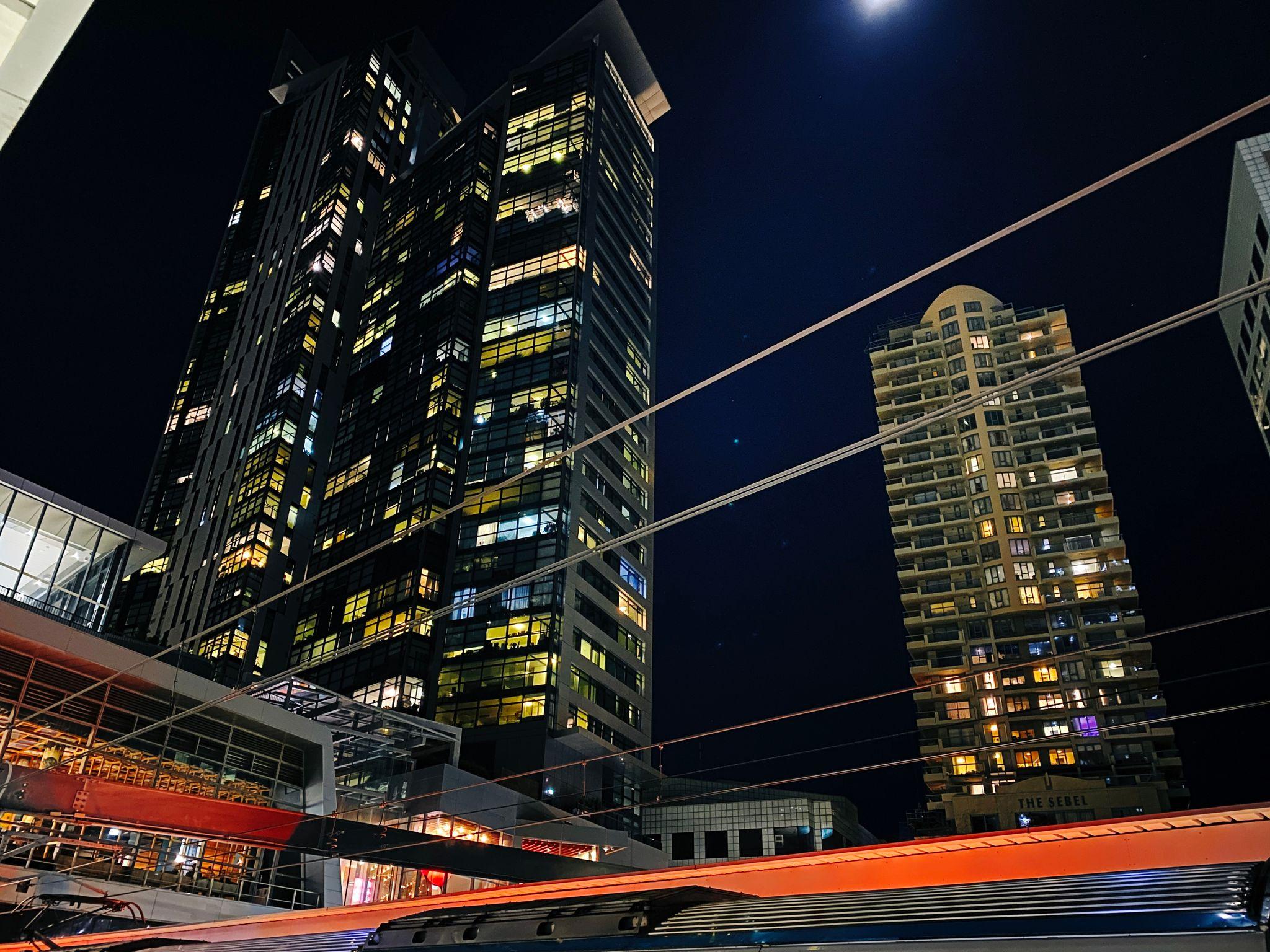 A photo taken at night time looking up at big apartment blocks.