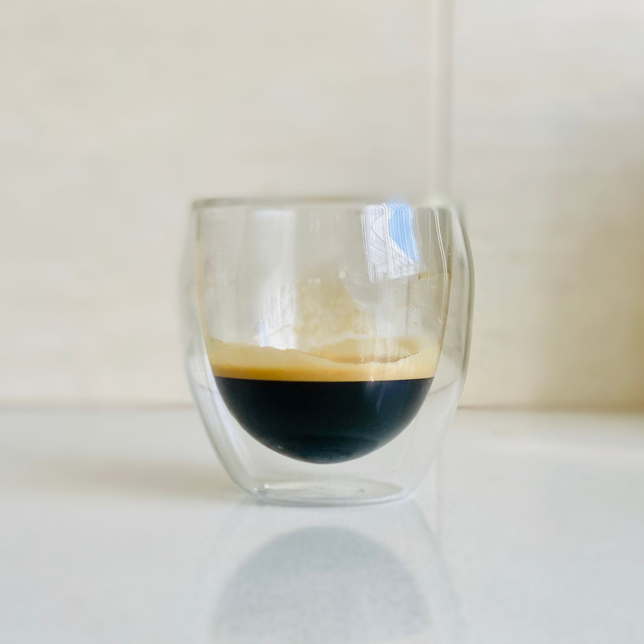 A photo of a short glass with espresso in it, it's curved on the outside and is double-walled with an even more pronounced curve on the inside walls where the liquid sits. The espresso looks like it's floating.
