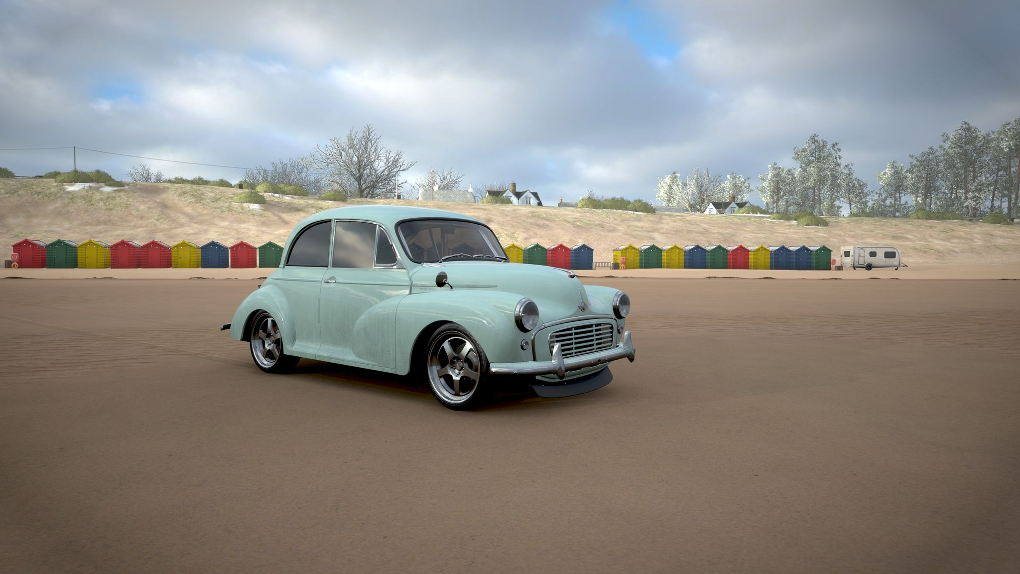 A screenshot from Forza Horizon 4 showing a pale baby blue Morris Minor sitting on a beach in front of a row of those weird little beach hut things the Poms love. The car has been lowered and has big shiny chrome rims to go with the shiny chrome front and rear bumpers.