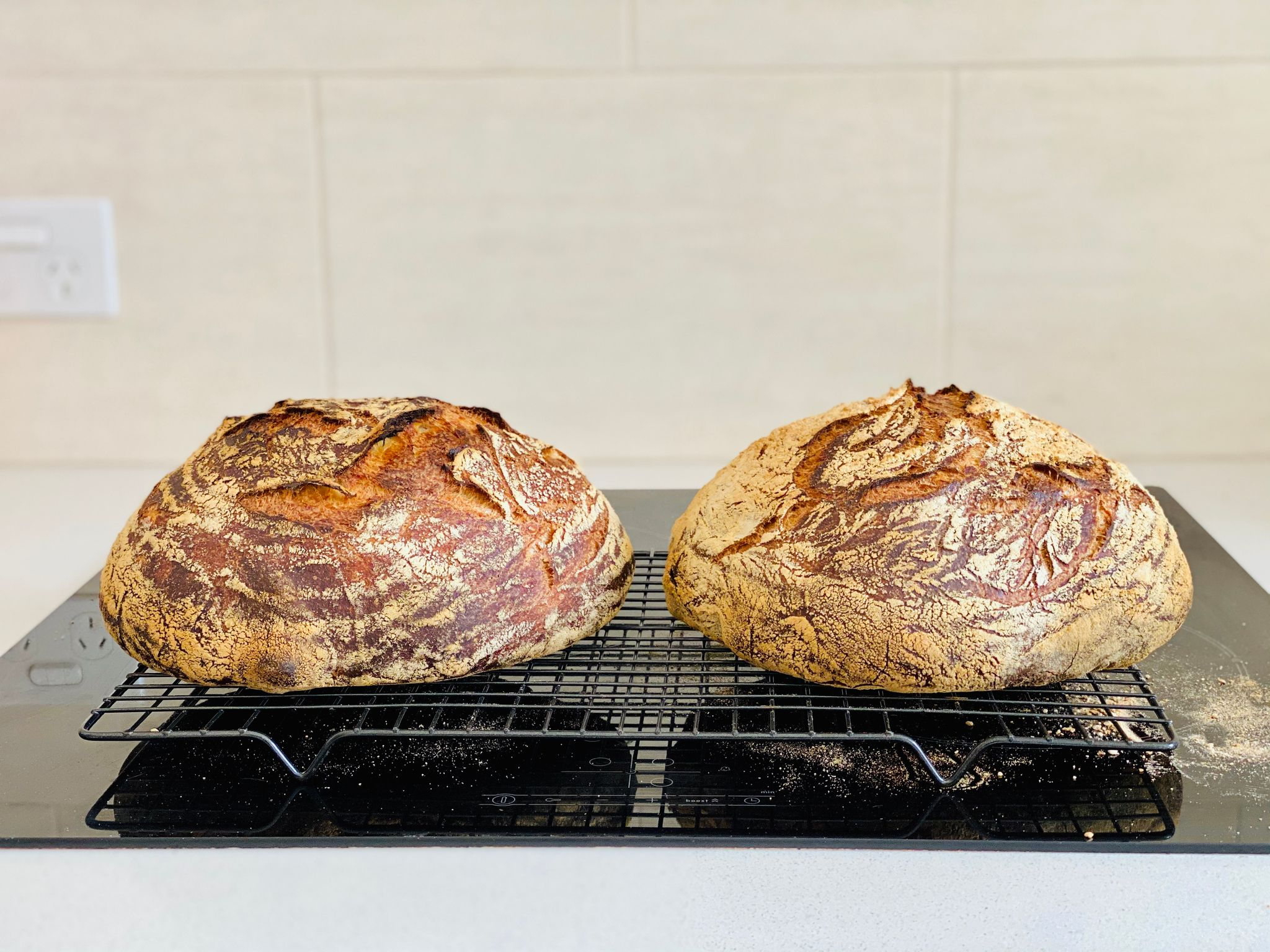 A photo of two dark brown loaves of bread sitting on a cooling rack.