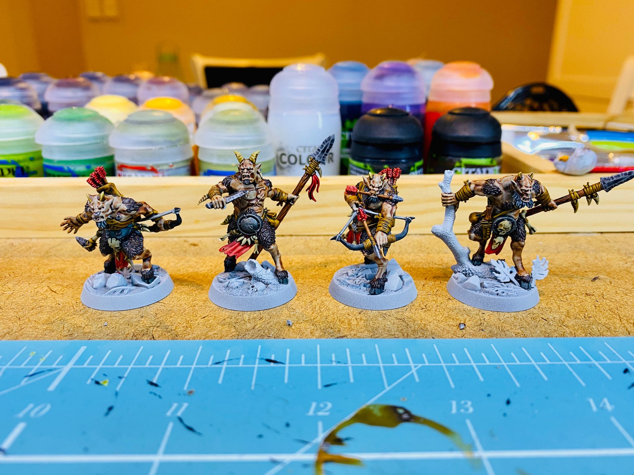 A photo of four goatmen miniatures in various poses.