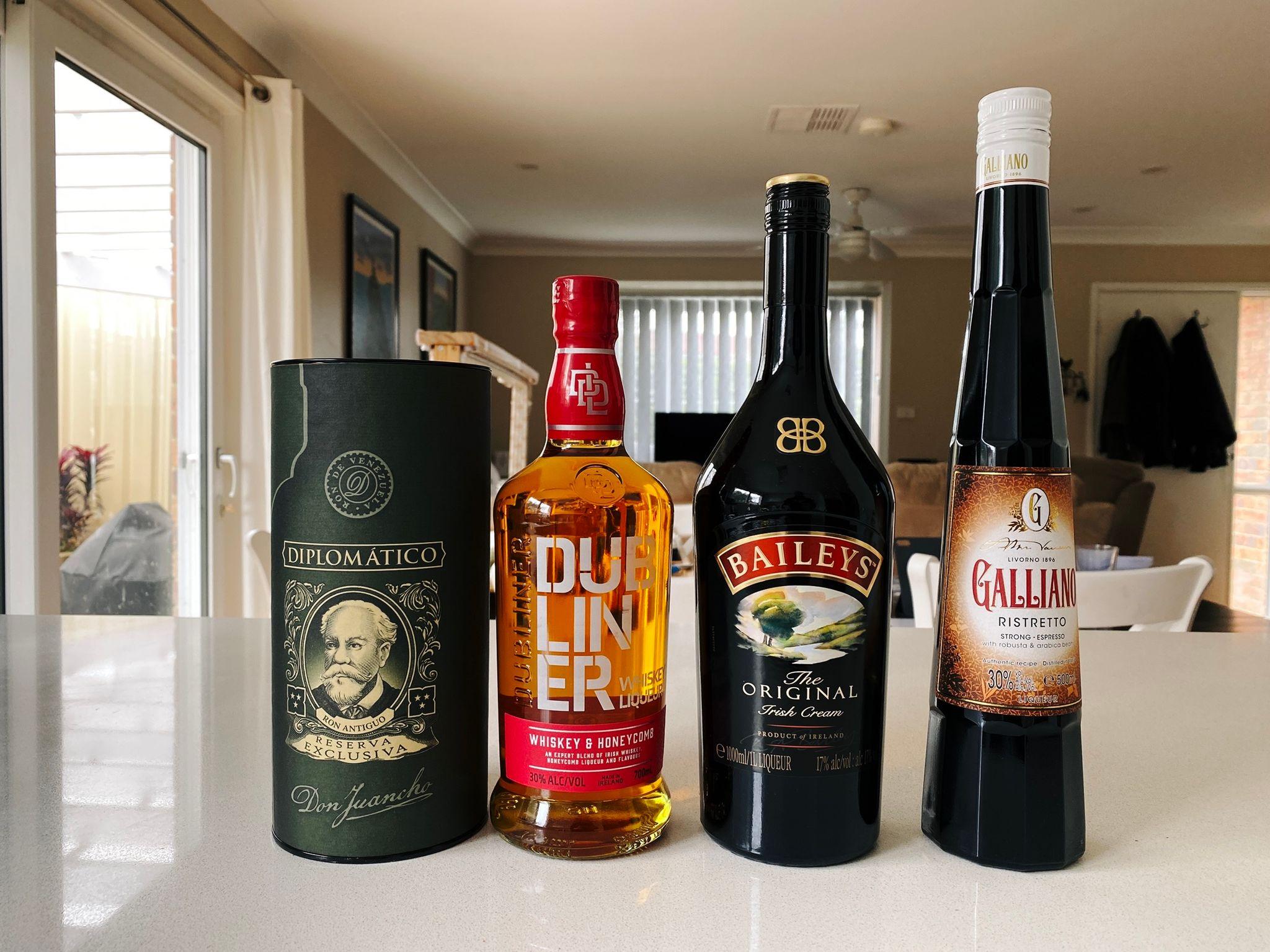 "A photo of four bottles of alcohol: ""Diplomatico""-brand dark rum, ""Dubliner"" whiskey/honeycomb liqueur, Baileys Irish Cream liqueur, and Galliano Ristretto coffee liqueur."